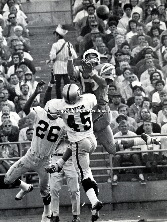 San Diego Charger receiver Lance Alworth catches pass against the Raiders Dave Grayson and Nemiah Wilson.(1969.Photo by  Ron Riesterer)
