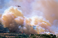 870000372 a los angeles county fire fighting helicopter flies above a burning hillside in the path of the topanga fire in the hills above the san fernando valley in southern california