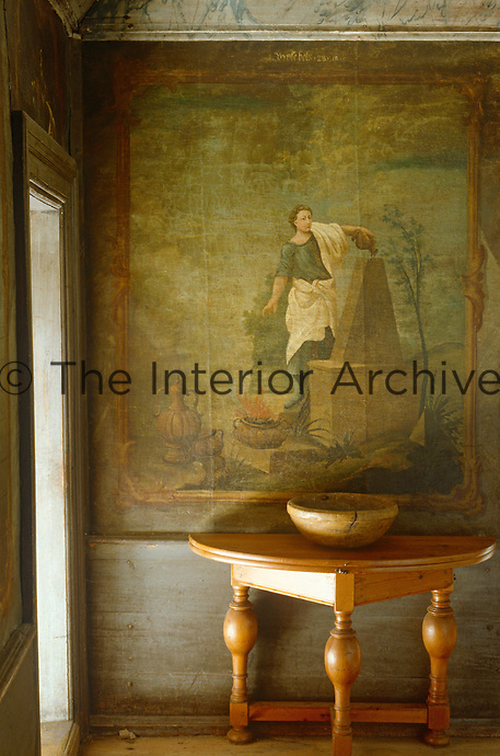 An antique console table has been placed in front of a faded mural in the entrance hall