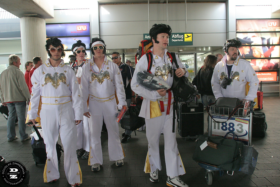 "USA National Soccer Team fans, (left to right) Billy Ryan of Kansas City, MO, Barry Ryan of Kansas City, MO, Chris Widmer of Columbia, MO, Pat Ryan of Kansas City, MO, and Philippe Lechevin of Kansas City, MO, dressed up in flight suits as the American Icon Elvis, look for transportation to the airport train station after exiting customs at Düsseldorf Airport. The group was traveling by train to Cologne, Germany and their hotel. They arrived at Düsseldorf Airport in Germany on Saturday morning, June 10th, 2006 after an overnight flight from JFK airport in New York City.  The fans were part of a tour group arraigned by Pat Ryan from Kansas City, MO called ""2006 World Cup Trip."" They were among the thousands of American fans who have descended on Germany to support the USA National team during the 2006 FIFA World Cup. The first game for the USA is against the Czech Republic in Gelsenkirchen on Monday June 12th."