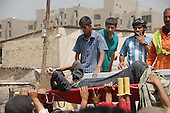 BAGHDAD, IRAQ: Men pull an injured woman from the rubble after a bomb explosion in the Alawi neighborhood, a Shia area in Baghdad...Bombs destroyed seven buildings in three areas of the Iraqi capital Baghdad, killing at least 28 people and wounding 75.