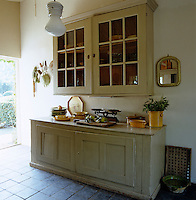 Painted kitchen cupboards designed in the style of a rustic dresser provide flexible storage