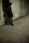 A woman in black coat and striped stockings stands alone, leaning against a wall in Venice, Italy