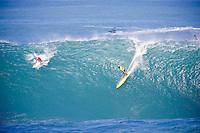 Kelly Slater (USA) and Bruce Irons (HAW) on his winning 100 point wave. The 2004 Quiksilver Eddie Aikau Big Wave Invitational won by Hawaiian surfer Bruce Irons (HAW) from the island of Kauai was held in 30 to 40' waves at Waimea Bay on the North Shore of Oahu Hawaii, today, December 15th 2004. Irons rode one of the biggest waves of the day which was at least 30' in height, taking home US$55,000 in prize money.  Photo: Joliphotos.com