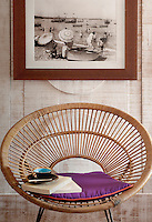 A framed vintage photograph hangs on the limed wood panelling of the television room above a 1960s wicker chair