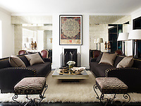 In the sitting room a pair of 1940s French stools are upholstered in a Brunschwig & Fils linen, the 1970s Belgian cocktail table holds a large ceramic bowl from Tomasz Starzewski and artwork by Shepard Fairey hangs above a bronze fire screen by Charles Edwards. A pair of early-20th-century Louis XVI–style chairs stand against one wall. The statues of monks were obtained in Singapore. The walls are sheathed in antiqued-mirror panels, which create a sense of space and the floors are ebonized oak.