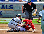 29 May 2011: San Diego Padres catcher Kyle Phillips tags a sliding Laynce Nix out at the plate in the bottom of the 6th inning during game action against the Washington Nationals at Nationals Park in Washington, District of Columbia. The Padres defeated the Nationals 5-4 to take the rubber match of their 3-game series. Mandatory Credit: Ed Wolfstein Photo