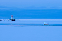 Salmon fishermen fish from a boat in a narrow strip of open water on Lake Superior in early spring in Marquette, Michigan.