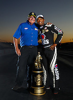 Nov 13, 2016; Pomona, CA, USA; NHRA top fuel driver Anson Brown (right) and National Dragster photographer Jerry Foss pose for a portrait with the world championship trophy following the Auto Club Finals at Auto Club Raceway at Pomona. Mandatory Credit: Mark J. Rebilas-USA TODAY Sports