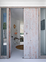 A simple distressed large wooden door opens into the whitewashed entrance hall of the house