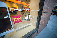 Signage on a window in a Well Fargo bank in New York informs customers of their acceptance of the Apple Pay method of payment, seen on Saturday, December 13, 2014. The three major retailers that accept the mobile payments, McDonald's, Walgreens and Whole Foods have reported an increase in mobile payments since the introduction of Apple Pay. (© Richard B. Levine)