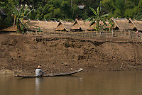 A man in a long boat and houses peppered with banana trees along the Nam Khan or Khan River in Luang Prabnag, Laos. Luang Prabang is on UNESCO's World Heritage list as it's an outstanding example of the fusion of traditional architecture and Lao urban structures with those built by the European colonial authorities...