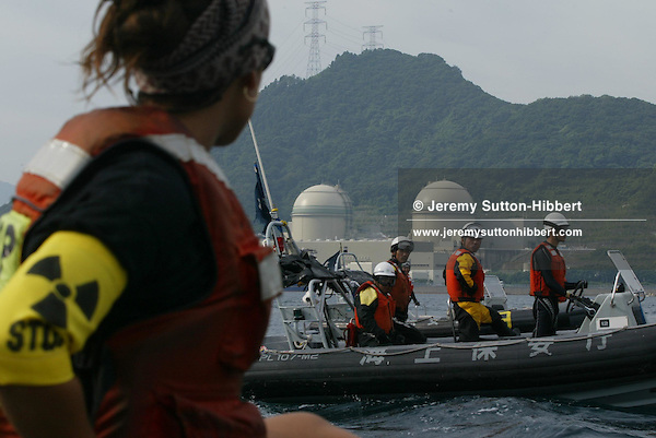 WATCHED BY JAPANESE POLICE ,GREENPEACE SHIP 'ARCTIC SUNRISE' AND INFLATABLES PROTEST IN UCHIURA BAY, BESIDE THE TAKAHAMA NUCEAR PLANT, AS BNFL SHIP 'PACIFIC PINTAIL' ARRIVES EARLY MORNING FOR RETRIEVAL OF REJECTED PLUTONIUM MOX FUEL, FOR SHIPMENT BACK TO THE UNITED KINGDOM. TAKAHAMA, JAPAN. 04/07/02. .PIC © JEREMY SUTTON-HIBBERT/GREENPEACE 2002..*****ALL RIGHTS RESERVED. RIGHTS FOR ONWARD TRANSMISSION OF ANY IMAGE OR FILE IS NOT GRANTED OR IMPLIED. CHANGING COPYRIGHT INFORMATION IS ILLEGAL AS SPECIFIED IN THE COPYRIGHT, DESIGN AND PATENTS ACT 1988. THE ARTIST HAS ASSERTED HIS MORAL RIGHTS. *******