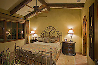 Quaint bedroom with paned windows and wrought iron bed
