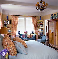 In the bedroom a pair of brass etageres topped with late 19th century Sevres vases flanks a 1950s American sofa