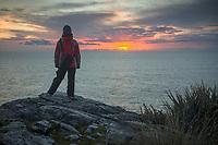 Woman watching sunset on wild coastline at Charleston near Westport, West Coast, New Zealand