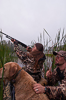A young female waterfowl hunter takes a shot at passing ducks from a blind.