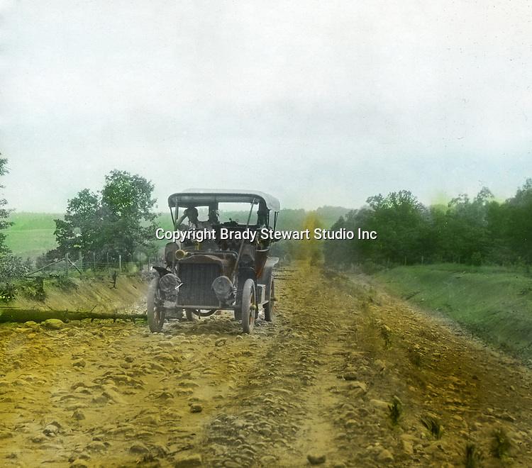 Greensburg PA:  The 1906 Buick Model F broken down after running over a tree on a rocky road outside Greensburg PA - 1906.  To give family and friends a better feel for the adventure, he hand-color black and white negatives into full-color 3x4 lantern slides.  The Process:  He contacted a negative with another negative to create a positive slide.  He then selected a fine brush and colors and meticulously created full color slides.