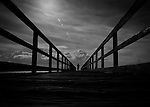 A man in silhouette at the end of a long pier looking into the clouds.