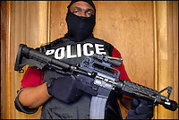 A member of the Selma Police Department Narcotics Division holds a Colt semi automatic 9mm carbine on the third floor of the Selma Police department.