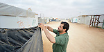 A man makes a fence of black plastic beside his home in the Zaatari refugee camp near Mafraq, Jordan. Established in 2012 as Syrian refugees poured across the border, the camp held more than 80,000 refugees by 2015, and was rapidly evolving into a permanent settlement, with many refugees moving out of tents and into modular houses. The ACT Alliance provides a variety of services to refugees living in the camp.