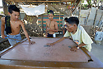 In Abucay, a seaside town in the Philippines province of Bataan, George Amarow (right) earns a living managing a billiard table in the town center. Born with scoliosis of the spine, Amarow is a member of the local Persons with Disabilities (PWD) organization.