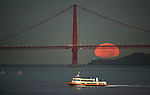 The full moon sets behind the Golden Gate Bridge as seen from Treasure Island in San Francisco, California.