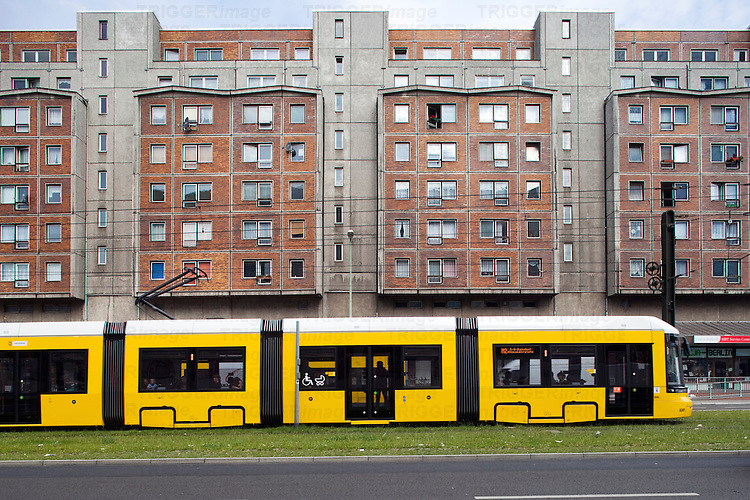 Tram in front of an apartment building on Karl-Liebknecht street, Berlin, Germany