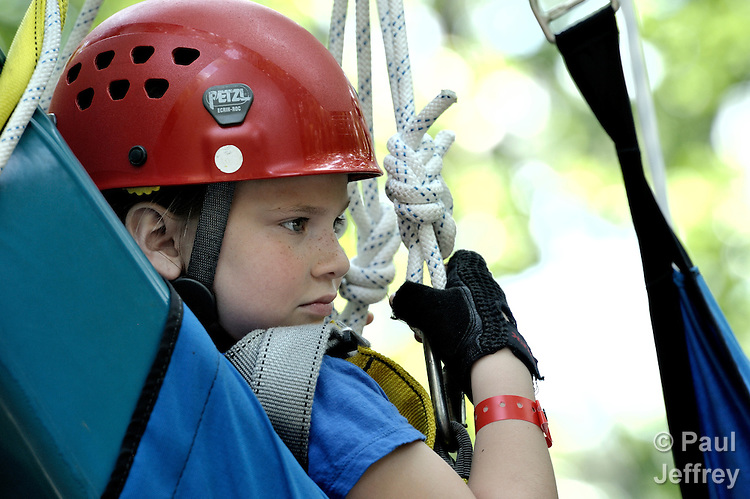 Camper Kaylee Ferguson is lifted onto a zip line at Camp Aldersgate in Little Rock, Arkansas. The camp, supported by United Methodist Women, offers children suffering from a variety of disabilities a safe and fun experience similar to that which normally-abled children often enjoy. The zip line uses a specially designed chair which accommodates children of differing physical abilities.