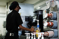 07/23/2015. A McDonald's worker serves a beverage on a restaurant in New York , the state fast food workers' wages will eventually rise to $15 (£9.60) an hour. Kena Betancur/VIEWpress