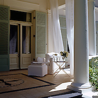 An armchair and footstool in white loose covers shielded by billowing sheer curtains enjoy a welcome shade in the lea of the columned portico