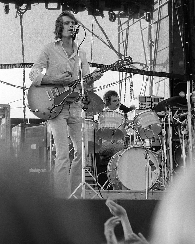 Bob Weir at the PA Cancelling Dual Microphone(s). The Grateful Dead in Concert at Dillon Stadium on 31 July 1974. Bill Kreutzmann on the Drum Kit behind Bob. Photograph taken with a Nikon FTn Camera and Tri-X B&W Film.