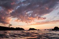 The colors of a vivid sunset reflect off the water at Waimea Bay, North Shore, O'ahu.