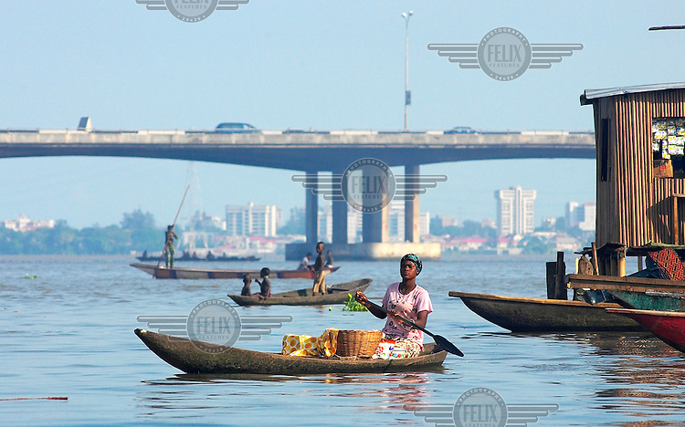A woman paddles her canoe in front of the third mainland bridge.