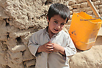 A boy poses shyly for a portrait in the village of Deh-e- Chowkay, in the Arghandab valley near Kandahar, Afghanistan. May 22, 2010. DREW BROWN/STARS AND STRIPES