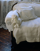 The severe edges of a Victorian sofa are softened by the starched white decorative linen and lace used to cover it