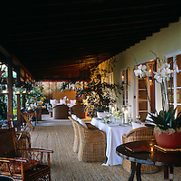 Wicker furniture provides comfortable sitting and dining areas on this wide covered terrace