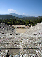 EPIDAURUS, GREECE - APRIL 14 : A narrow angle view from above of the Theatre, on April 14, 2007 in Epidaurus, Greece. The Theatre, designed by Polykleitos the Younger, was built in the late 4th century BC and extended in the Hellenistic period. It was rediscovered in 1881 and significantly restored in the 1950s.  It has the three main features of a Greek theatre: the orchestra, a sunken round stage; the skene, a raised rectangular stage; and the cavea, a raked semi-circular auditorium with radiating diazomas. The theatre is renowned for its accoustics thanks to the symmetry of the cavea, and for its beautiful mountain view, seen here in the afternoon light. (Photo by Manuel Cohen)
