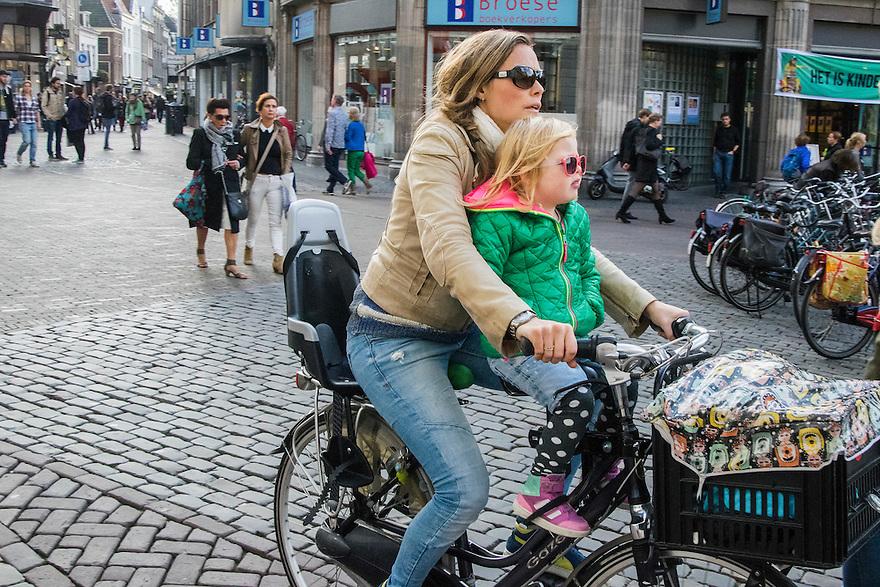 Nederland, Utrecht, 10 okt 2014<br /> Mensen op straat. Moeder met kindje in fietszitje voor op de fiets. <br /> Foto: (c) Michiel Wijnbergh