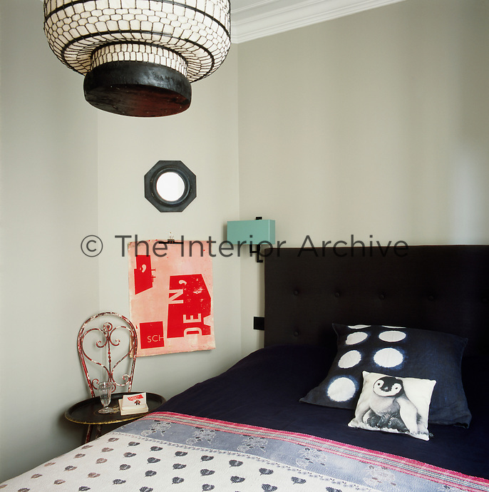 A guest bedroom has a slightly retro feel as seen in the light fittings. The bed has an upholstered headboard