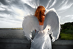 Young woman wearing angel wings spread open, a dark scene. Taken at Levy Park and Preserve, Long Island, New York, USA.