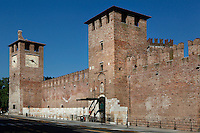Low angle view of the main entrance, the covered towers, and the mighty remparts of Castelvecchio, 1354-79, Verona, Italy. The castle, built with its bridge, for Cangrande II, stands on the probable site of a Roman fortress. The castle, where Napoleon stayed, was damaged  during the Pasque Veronesi, Napoleonic Wars (1796-97). Castelvecchio was restored in 1923 and 1963-65. Picture by Manuel Cohen.