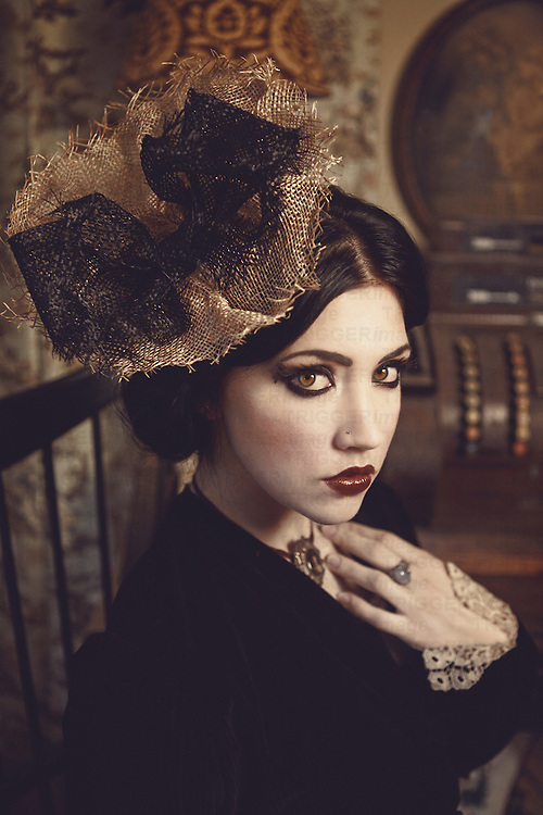 A beautiful pale young woman in fancy old-fashioned clothes and vintage hat looking at camera