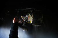 """Al Tuam, Gaza Strip, Jan 21 2009.Alham Al Sultan, 30, wipes away the sooth covering a portrait of Yasser Arafat on the family living room wall. .She says: """"The palestinian people died when Yasser Arafat died""""..Inhabitants slowly come back to heavily damaged or totally destroyed homes, as fierce fighting between the Israeli army and Hamas took place in this elevated area just north of Gaza city.."""