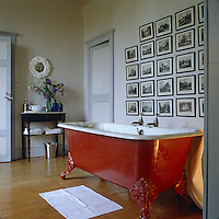 A red-oxide painted ball-and-claw bath sits below a wall covered in a collection of black and white framed engravings of Scottish castles