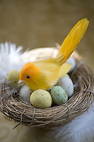 Detail of an Easter decoration of a chick in a nest of small speckled Easter eggs