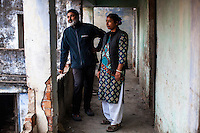 Ajeet Singh, founder of Guria Swayam Sevi Sanstan NGO and his wife and partner, Santwana Manju, look around as they pose for a portrait in one of the largest brothels they have raided and closed down in the Shivdaspur red light area in Varanasi, Uttar Pradesh, India on 25 November 2013.