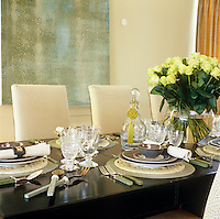 Accents from the large oil painting behind are echoed in the fabric of the dining chairs and in the jade green colour of china and cutlery in this dining room