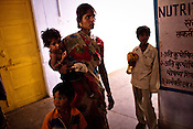 24 year old Jaikunwar with her 9 year old son, Mahendra (left) and her malnutritioned 15 month old daughter, Anjana are seen outside the 'Nutritional Reahabilitation Centre' at the pediatrics section of Community Health Centre (Block Hospital) in Talbehat, Uttar Pradesh, India. The Indian government spends $1.4 billion a year - on programs that include weighing newborn babies, counseling mothers on healthy eating and supplementing meals, but none of this is yeilding results. According to UNICEF, some 48% of Indian children, or 61 million kids, remain malnourished, the clinical condition of being so undernourished that their physical and mental growth are stunted. Photo: Sanjit Das/Panos for The Wall Street Journal.Slug: IMALNUT