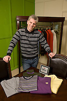 Boss of a cashmere sweater company wwith some of his products in the boardroom
